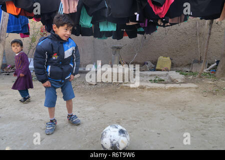 dpatop - 06 December 2018, Afghanistan, Kabul: Murtasa Ahmadi plays football in a courtyard. Two years ago, the little football fan Murtasa Ahmadi from Afghanistan was a worldwide star on the Internet with his homemade Messi jersey. Now the now seven-year-old boy and admirer of the Argentine footballer Lionel Messi fled with his family from his home district Dschaguri to the capital Kabul.  (to dpa: 'Little Messi-fan escaped from Taliban to Kabul' from 06.12.2018) Photo: Veronika Eschbacher/dpa - Stock Photo