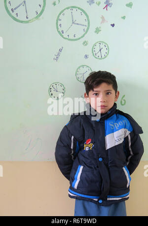 06 December 2018, Afghanistan, Kabul: Murtasa Ahmadi (r) is standing in a room. Two years ago, the little football fan Murtasa Ahmadi from Afghanistan was a worldwide star on the Internet with his homemade Messi jersey. Now the now seven-year-old boy and admirer of the Argentine footballer Lionel Messi fled with his family from his home district Dschaguri to the capital Kabul. (to dpa: 'Little Messi-fan escaped from Taliban to Kabul' from 06.12.2018) Photo: Veronika Eschbacher/dpa - Stock Photo