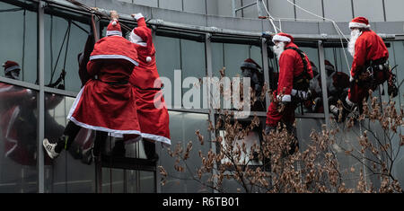 Berlin, Germany. 06th Dec, 2018. Men and women dressed as Santa Clauses are preparing for their mission on the roof of the Charité Children's Hospital. From the roof of the building they roped down to the children, who waited on their stations at the windows. Afterwards the St. Nicholas visited the stations and presented presents. Credit: Paul Zinken/dpa/Alamy Live News - Stock Photo