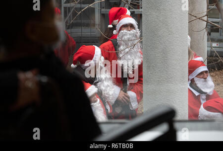 Berlin, Germany. 06th Dec, 2018. Women and men dressed as Santa Clauses stand in the courtyard of the Charité Children's Hospital. Previously they had roped down with ropes from the roof of the building to the children, who greeted the guests at the stations at the windows. Afterwards the St. Nicholas visited the stations and presented presents. Credit: Paul Zinken/dpa/Alamy Live News - Stock Photo