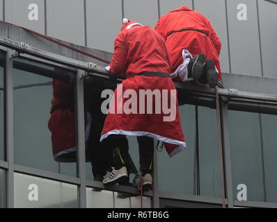 Berlin, Germany. 06th Dec, 2018. Men and women dressed as Santa Clauses are reflected in a glass façade and prepare for their mission on the roof of the Charité Children's Hospital. From the roof of the building they roped down to the children, who waited on their stations at the windows. Afterwards the St. Nicholas visited the stations and presented presents. Credit: Paul Zinken/dpa/Alamy Live News - Stock Photo