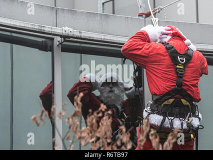 Berlin, Germany. 06th Dec, 2018. A man dressed as Santa Claus is reflected in a glass façade and prepares for her mission on the roof of the Charité Children's Hospital. From the roof of the building they roped down to the children, who waited on their stations at the windows. Afterwards the St. Nicholas visited the stations and presented presents. Credit: Paul Zinken/dpa/Alamy Live News - Stock Photo
