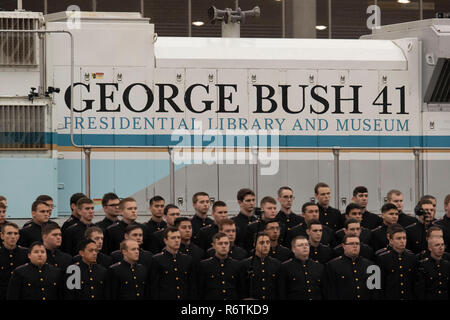 Somber members of Texas A&M University's Singing Cadets stand in front of the train carrying the casket of former President George H.W. Bush upon its arrival from Houston at Texas A&M University for burial at the George Bush Library on campus. - Stock Photo