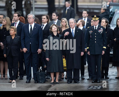 Former Pres. George W. Bush and wife Laur (center), Jeb Bush and wife Paloma (left) and other family members stand at attention as a military honor guard carries the casket of Bush's father, former President George H.W. Bush, to a hearse before burial at the nearby George Bush Library - Stock Photo