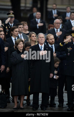 Former Pres. George W. Bush, wife Laura, and other family members stand at attention as a military honor guard carries the casket of Bush's father, former President George H.W. Bush, to a hearse before burial at the nearby George Bush Library - Stock Photo