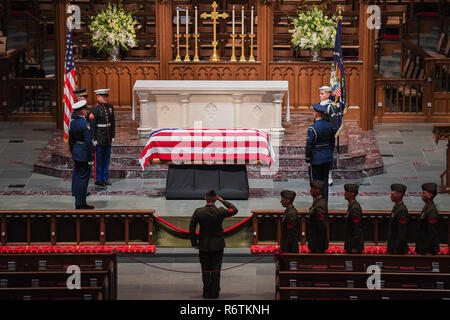 A U.S. Marine salutes the flag draped casket of former president George H.W. Bush resting instate at his home church of Saint Martins Episcopal following the State Funeral in Washington December 6, 2018 in Houston, Texas. Bush, the 41st President, died in his Houston home at age 94 and will be buried at his presidential library at Texas A&M University. - Stock Photo