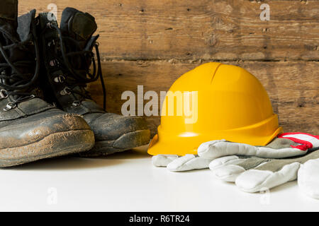 Equipment safety standard. Yellow hard hat, construction boots and gloves. - Stock Photo