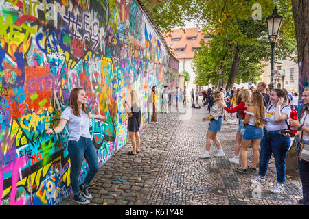 Lots of people taking photos at the Prague Lennon Wall Lennonova zeď Prague Velkopřevorské náměstí, Malá Strana Prague Czech Republic Europe - Stock Photo