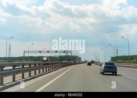 View of paved freeway with lanterns on sides and cars driving among green summer trees in cloudy day - Stock Photo