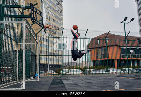 basketball player playing on the street - Stock Photo