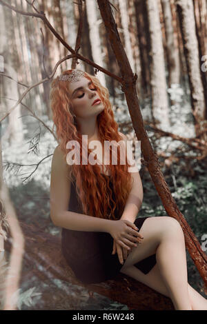 Romantic woman with red hair lying in the grass in the woods. A girl in a light black dress sleeps and dreams in a magical forest - Stock Photo