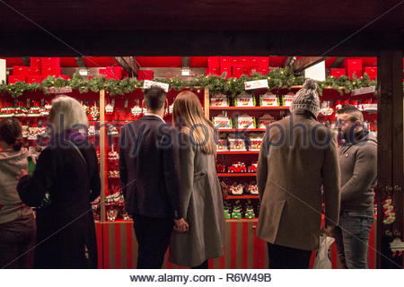London, UK - December 2: couple and visiting a stalls of the  Christmas Market in Leicester Square on December 2, 2018 in London, UK - Stock Photo