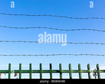 Barbed wire on fence against blue sky. Symbol of unfreedom and deprivation. Unfreedom concept. - Stock Photo