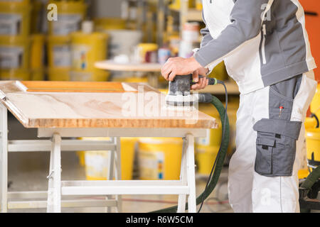 a painter at the wooden door grinding - Stock Photo