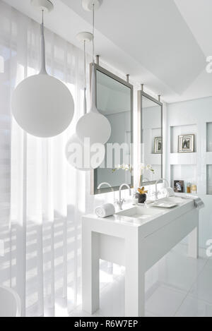 Double basins with silver mirror frames and white pendant shades in new build villa, Quinta do Lago - Stock Photo