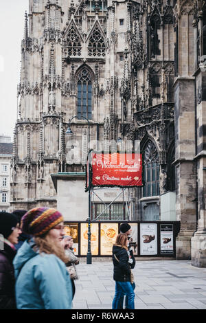 Vienna, Austria - November 24, 2018: People walking past directional sign to Christmas market stall near St. Stephen Cathedral, the most important rel - Stock Photo