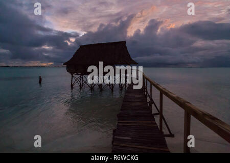 Traditional overwater thatched roof bungalow hut in lagoon of South Tarawa atoll, night, evening, twilight, sunset, Kiribati, Micronesia, Oceania. - Stock Photo