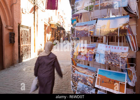 Marrakech tourism - a local woman walks past a shop selling postcards in the souk, Marrakesh Medina, Morocco North Africa