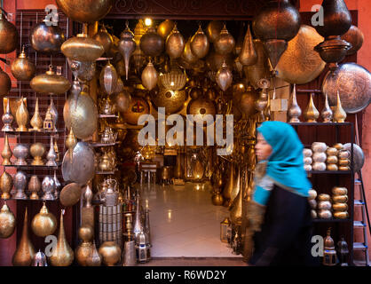 Marrakech souk - a local arab woman walking past a craft shop, Marrakesh medina, Morocco North Africa - Stock Photo