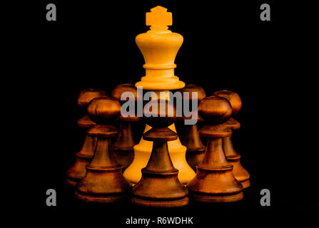 Under siege. White King beset by black enemies with sense of no escape, standard chess wooden piece on black background - Stock Photo