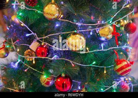 A Christmas ball hangs on the background of a clock. It's time for a new year. Multicolored glare and brilliance. Gold box - Stock Photo