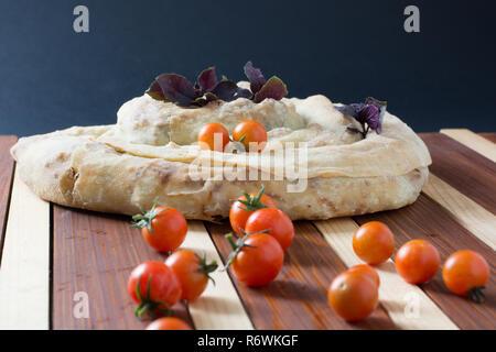spiral filo pie burek with cherry tomatoes - Stock Photo