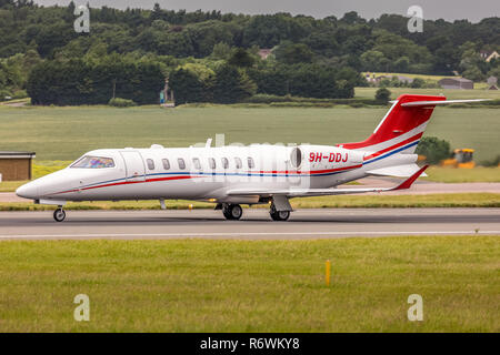 A Bombardier Learjet 75 corporate business jet aircraft, registered in Malta as 9H-DDJ, preparing for take off from London Luton Airport in England. - Stock Photo