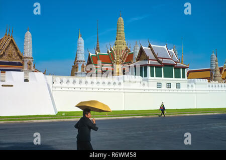 Pedestrians walking past the impressive skyline of Wat Phra Kaew (Gaew) and the Grand Palace in Bangkok, Thailand, the country's most revered temple - Stock Photo