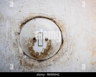 Old dirty light switch on white wall - Stock Photo