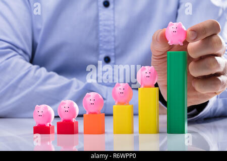 Businessperson Placing Piggy Bank On Top Of Business Graph - Stock Photo