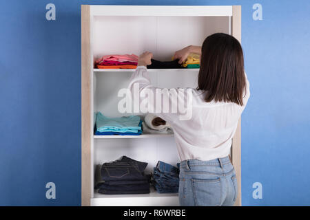 Woman Choosing Cloth From Shelf - Stock Photo