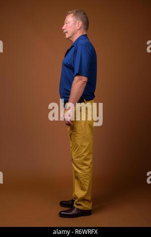 Full length profile view portrait of senior man standing - Stock Photo
