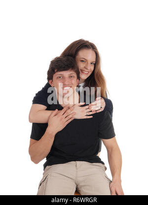 Young couple, she is hugging him from behind - Stock Photo