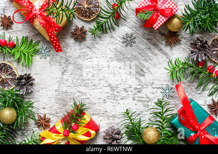 Christmas frame made of fir branches, gift boxes, red berries. cones and anise stars with dried oranges. Christmas composition. flat lay. top view - Stock Photo