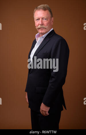 Handsome senior businessman with mustache wearing suit - Stock Photo