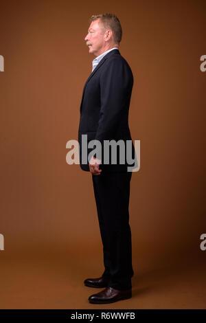 Full length profile view portrait of senior businessman standing - Stock Photo