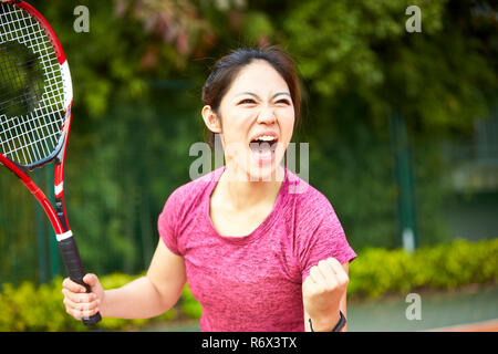 young asian girl female tennis player celebrating after scoring a point - Stock Photo