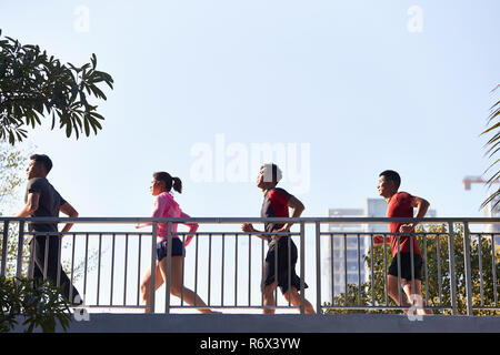 four young asian runner running in the morning passing through a footbridge. - Stock Photo