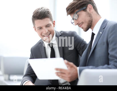 Image of two young businessmen using touchpad at meeting - Stock Photo