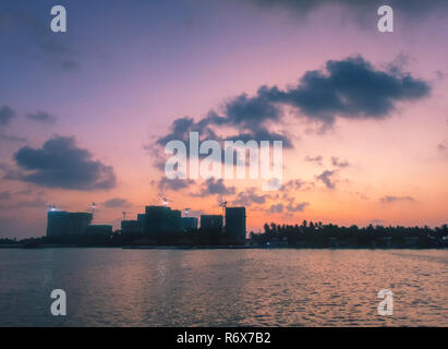 Sunrise and the silhouette of the skyline of Male in the Maldives - Stock Photo