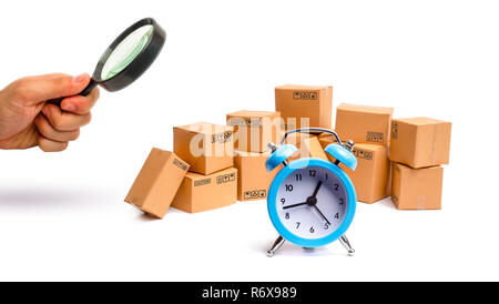 Magnifying glass is looking at the Cardboard boxes and clock on white background. Time of delivery. concept of buying and selling goods and services,  - Stock Photo