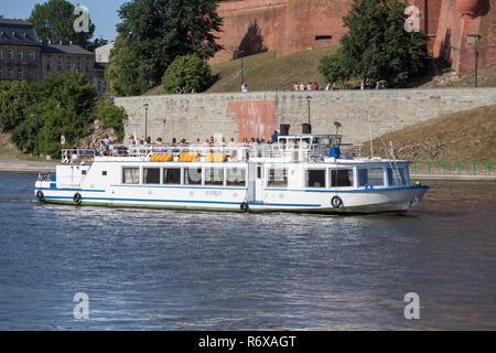 KRAKOW, POLAND - JUNE 9, 2018. Tourists in Motor boat Legend on Vistula River near Wawel Castle in Krakow - Stock Photo