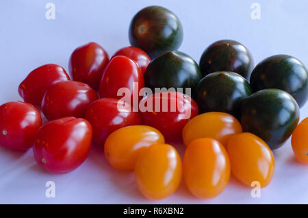 A variety of tomatoes in group on white background