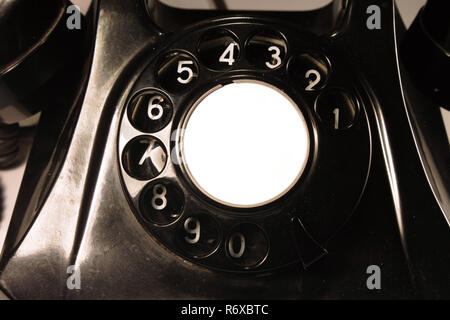 Close-up of the dial of a bakelite telephone, produced in the 1955 in Switzerland. Isolated on white background. - Stock Photo