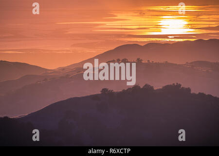 Beautiful rolling hills bathed in the sunset light; the setting sun reflected in the water of the San Francisco Bay in the background; view from Mt Ha - Stock Photo