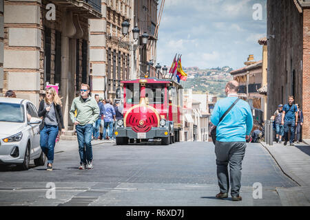 Toledo, Spain - April 28, 2018: Tourist strolling in a street of the historic district next to a small tourist red train on a spring day - Stock Photo