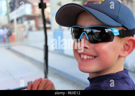 Cute red headed boy with sunglasses and hat turned to smile at camera while riding golf cart - Stock Photo
