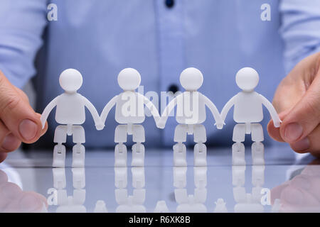 Person Holding Human Figure's Hand - Stock Photo