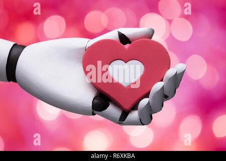 Robot Holding Red And White Heart - Stock Photo