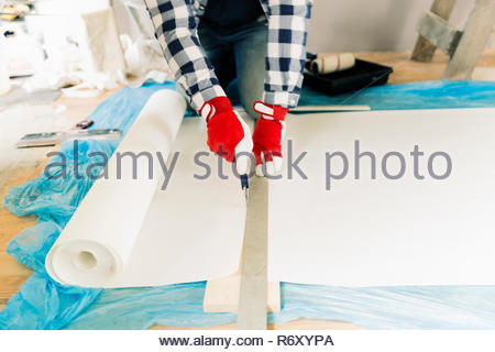 Handyman, worker measuring wallpaper to cut. Home renovation and repair concept - Stock Photo